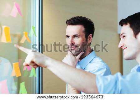 Young professionals discussing ideas written on sticky notes - stock photo