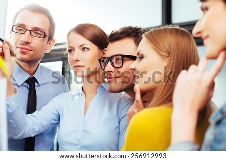 Young professionals looking at a board and writing on it - stock photo