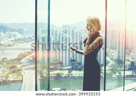 Young proud businesswoman is talking on her mobile phone with client and reading order on digital tablet, while is standing near office window with view of developed business district in China - stock photo