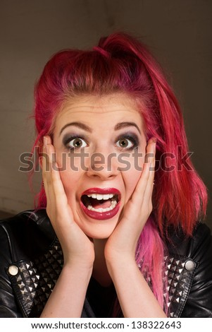 Young punk rocker female with hands on face - stock photo