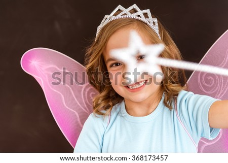 Young queen fairy with pink wings holding a magic wand against dark background, magic wand is close-up - stock photo