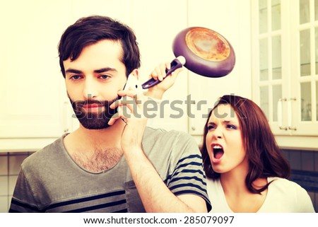 Young rage woman hitting her talking partner with frying pan. - stock photo