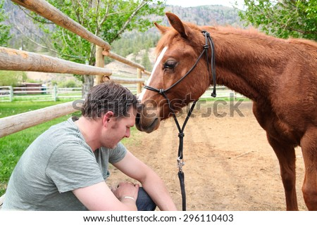 Young rancher and his trusting colt on ranch - stock photo