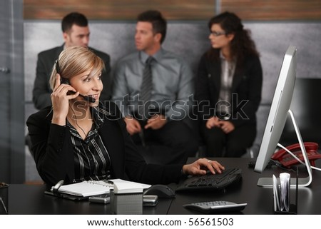 Young receptionist sitting at desk in office recepcion, talking on mobile phone, smiling, people waiting in background. - stock photo