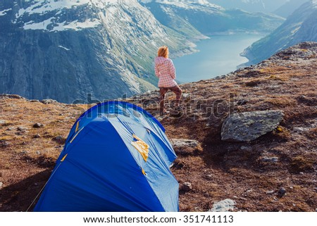 young red girl sneakers stands on a rock and watching the sunset and the mountains, overnight in tent a trip to the mountains, the language of the Troll, Norway fjords, cold weather - stock photo