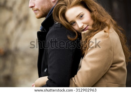 Young red hair couple at autumn park - stock photo