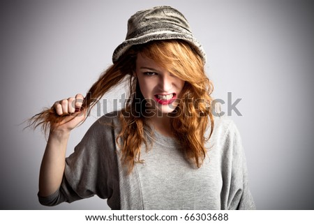 young red hair woman displeased with her hair, studio shot - stock photo