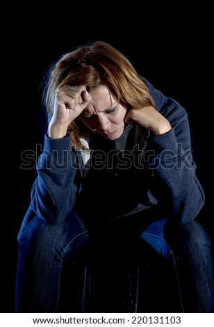 young red hair woman in casual clothes suffering depression and stress sitting alone in pain and grief  feeling sad , miserable and desperate isolated on black background - stock photo