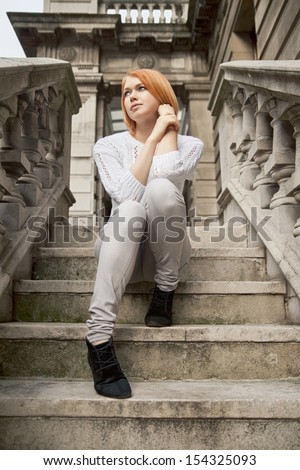 young red-haired beauty sitting on stairs oa Academy of Arts in London - stock photo