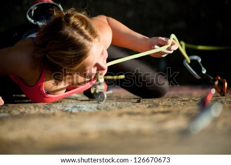 Young red-haired girl climbs on a rock with a belay - stock photo