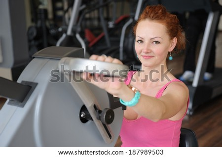 young red haired girl doing hands spinning machine workout - stock photo