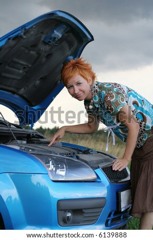 young red-haired woman with her broken car. The girl have a big problem - stock photo