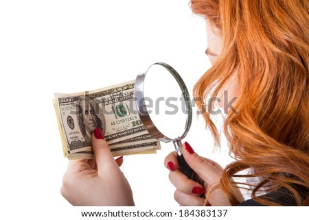 Young red head business woman holding magnifying glass and analyzing one hundred dollar banknotes, isolated on white background. - stock photo