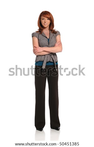 Young redhead businesswoman standing with arms crossed - stock photo