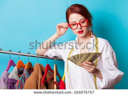 Young redhead designer with dollars and clothes on blue background - stock photo