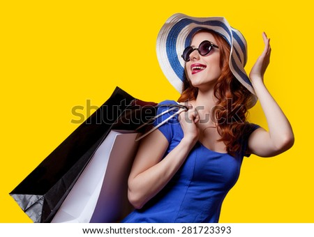 Young redhead girl in blue dress with shopping bags on yellow background. - stock photo