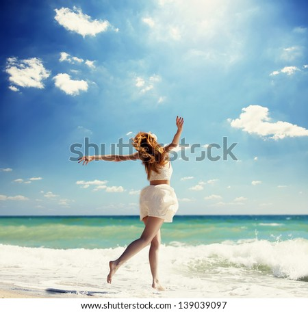 Young redhead girl jumping at the beach. - stock photo