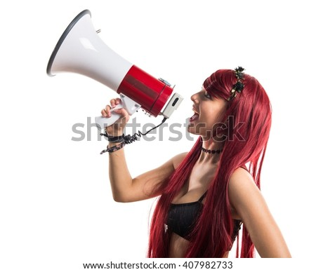 Young redhead girl shouting by megaphone - stock photo