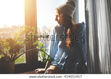 Young redhead hipster woman enjoying sunshine while sitting on the windowsill at home. Portrait of student girl contemplating sunrise through the window in the morning before classes at the university - stock photo