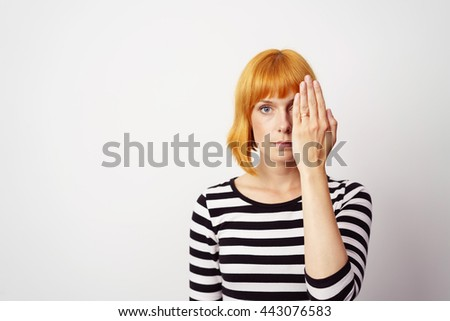 Young redhead woman covering one eye with her hand as she stares at the camera with a serious expression, over white with copy space - stock photo