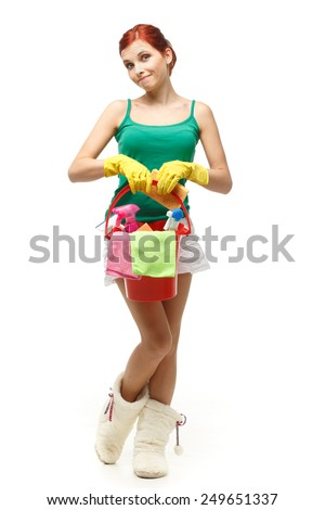 Young redhead woman is holding bucket with cleaning supplies on a white background. Housekeeping. Cleaning woman. - stock photo