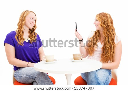 young redhead woman making photos of her cute friend on white background - stock photo