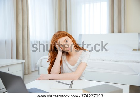 Young redhead woman sitting at the table with her homework at home and looking at camera - stock photo