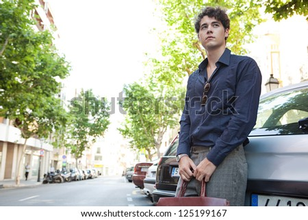 Young relaxed businessman leaning on a car, waiting while holding his leather briefcase and wearing elegant clothes. - stock photo