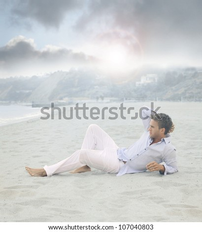 Young relaxed man laying on beach in calm blue morning light - stock photo