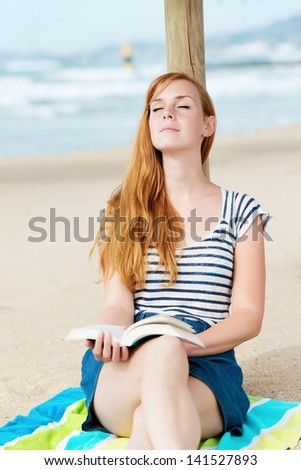 Young relaxed woman sitting with a book on the beach - stock photo