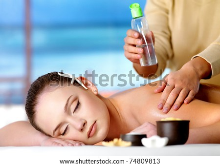 Young relaxing beautiful woman getting massage with cosmetic oil in spa salon - nature background - stock photo