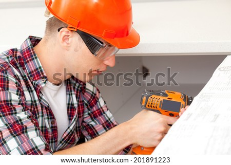 young repairman with electric drill in new apartment - stock photo