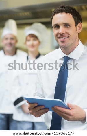 Young restaurant manager holding his tablet  smiling at the camera  - stock photo