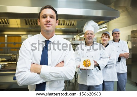 Young restaurant manager posing in front of team of chefs smiling at camera - stock photo