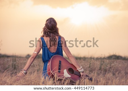 Young retro hippy styled woman with acoustic guitar in wheat field looking at sun to find inspiration for the next song. Music, art and lifestyle concepts.   - stock photo