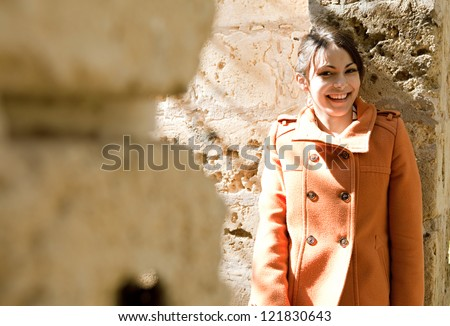 Young retro style woman wearing an orange coat and leaning on a sight's old stone walls while on vacation during a sunny day, smiling at the camera. - stock photo