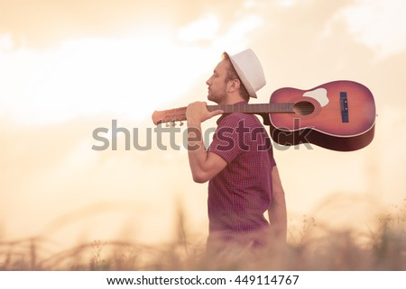 Young retro styled man with acoustic guitar over his shoulder walking through the wheat field. Sun and clouds in the background. Music, art and lifestyle concepts.   - stock photo