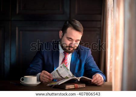young, rich, handsome, bearded man, a successful businessman reading a magazine in a cafe - stock photo