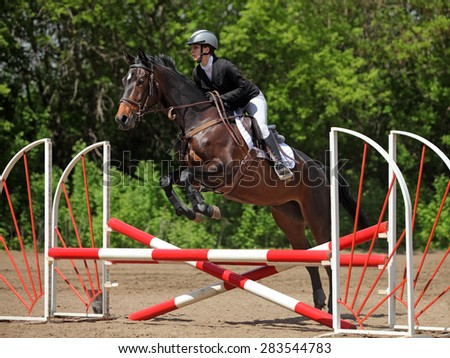 Young rider and her horse take part in local jumping competition  - stock photo