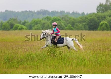 Young rider galloping on horseback Outdoors - stock photo