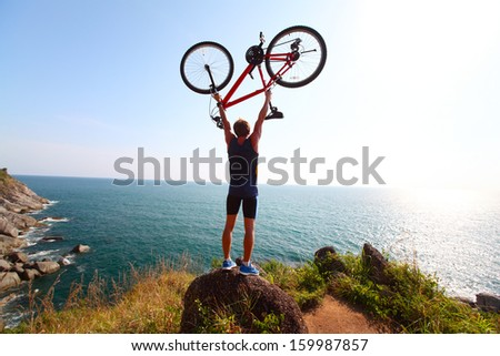 Young rider standing on top of a hill with sea view and holding the bicycle - stock photo