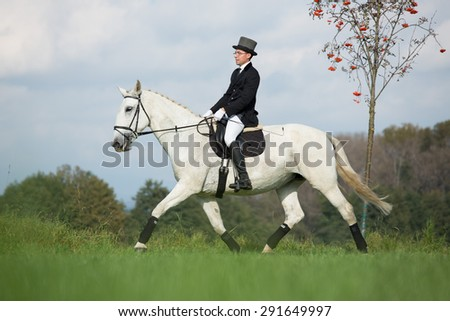 Young rider while training dressage with his horse  - stock photo