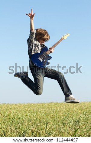 Young rocker posing with musical instrument outdoors at bright summer day - stock photo