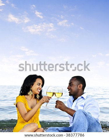 Young romantic couple celebrating with wine at the beach with copyspace - stock photo