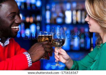 Young romantic couple enjoying cocktails in nightclub - stock photo