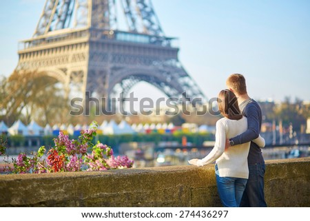 Young romantic couple in Paris having fun near the Eiffel tower - stock photo
