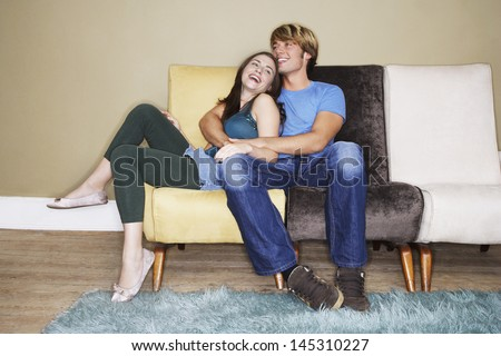 Young romantic couple laughing on sofa - stock photo
