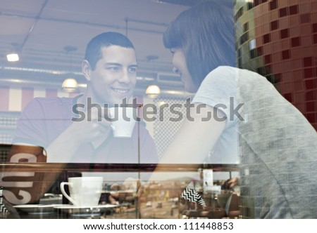 Young romantic couple shot through window enjoying coffee - stock photo