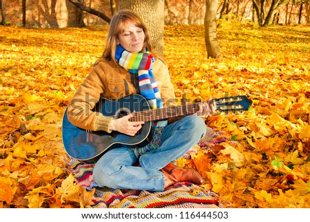 Young romantic girl sitting in autumn park with guitar - stock photo