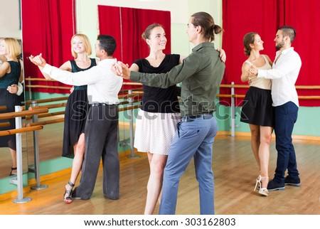 young russian men and women enjoying of tango in class  - stock photo